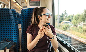 girl-in-train-listening-to-music-small