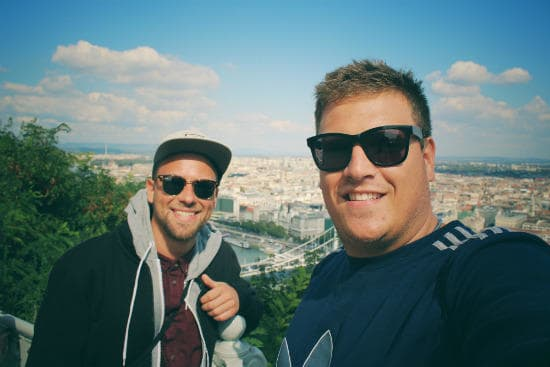 Interrail customer testimonials | Two young men taking a selfie with a cityview in the background