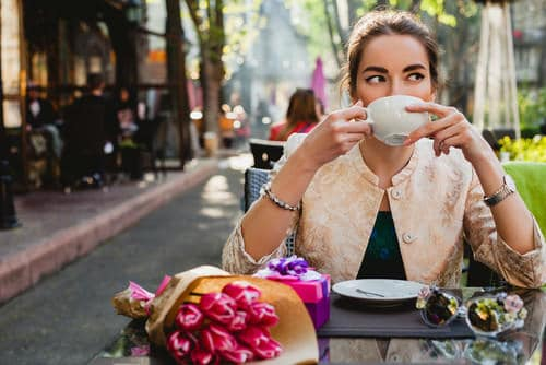 interrail_spring_trip_tile_image_-_young_stylish_woman_sitting_in_cafe_drinking_coffee_with_the_beautiful_pink_tulips_on_the_table_in_the_spring