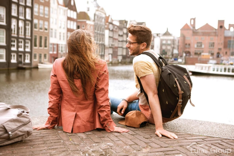 Image of a couple sitting on the edge of the canal in Amsterdam